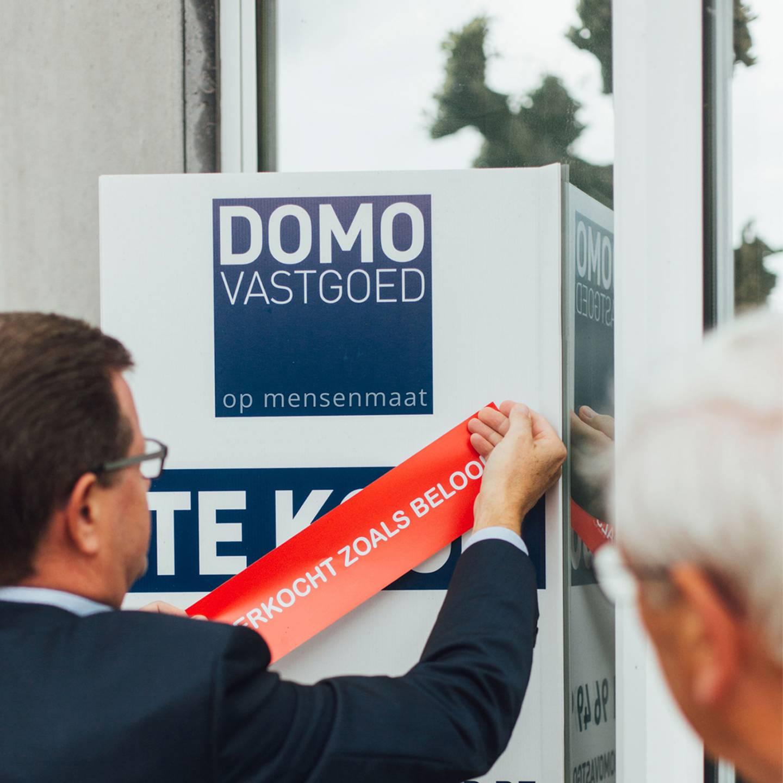 Foto van een man die een sticker aanbrengt op een reclampaneel van DOMO